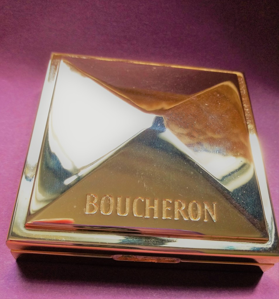 Boucher Trouble brass solid fragrance compact against a dark red background