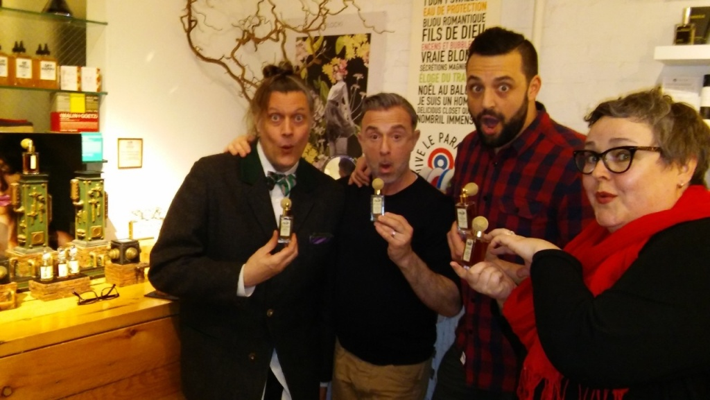 Four partygoers holding bottles of Euphorium Brooklyn perfume and making goofy surprised faces