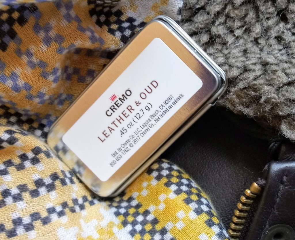 a tin of Cremo Leather & Oud fragrance, resting against a leather jacket and a plaid scarf