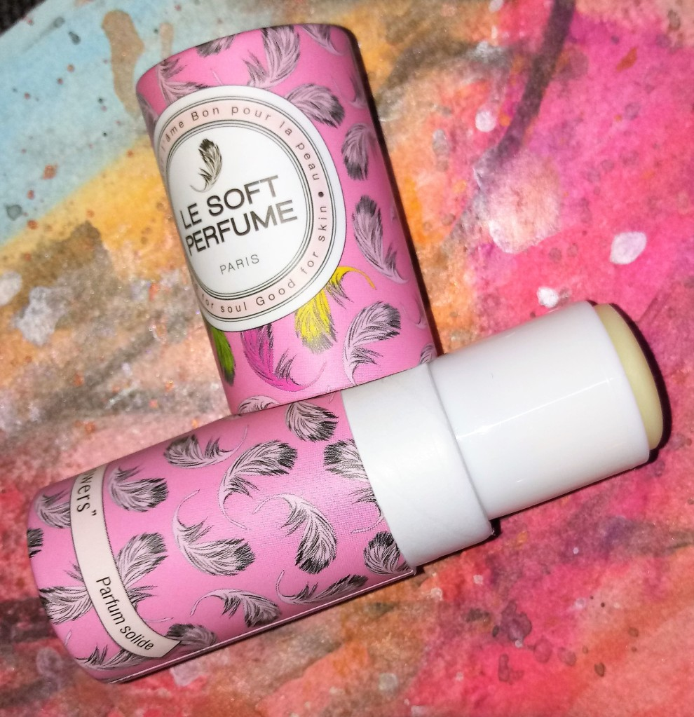 Striptease Flowers perfume uncapped, with the solid fragrance stick visible, against a multi-colored background