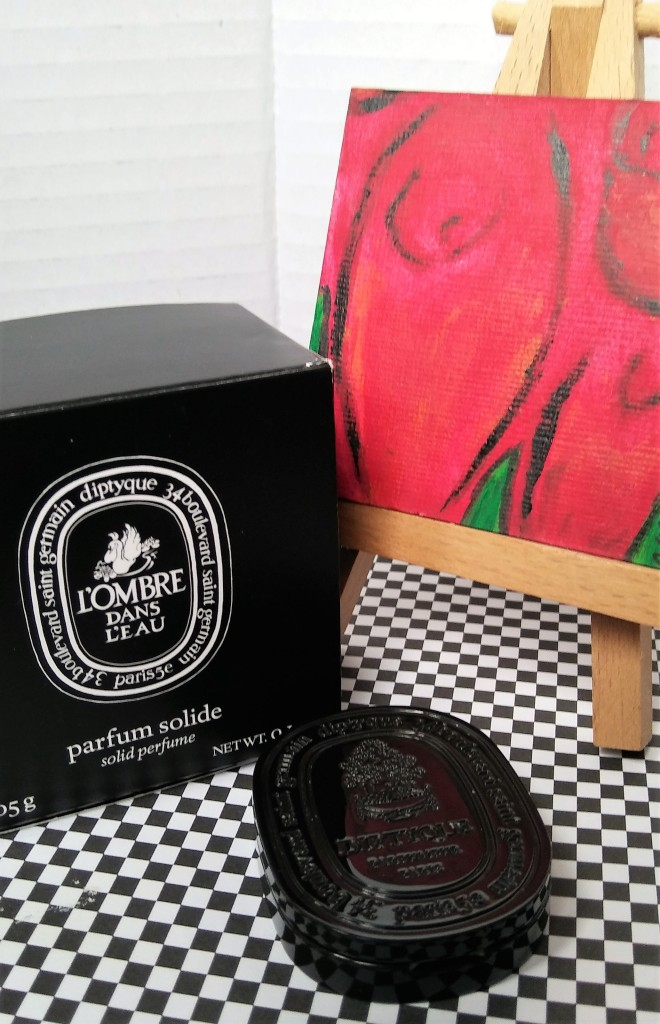 The L'Ombre dans L'eau solid perfume compact and box, next to a miniature painting of roses