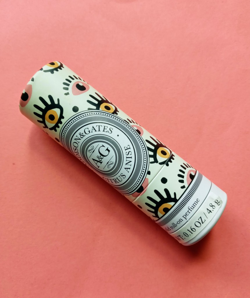 The Addison & Gates Citrus Anise solid perfume, in a beige tube printed with pink and coral eyes with bold eyelashes