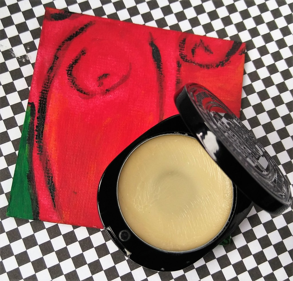 The perfume compact open to show the creamy texture of the solid, against a red painting and black and white background