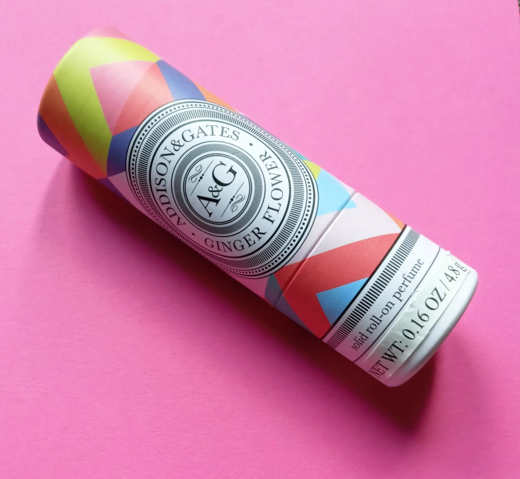 The Addison & Gates Ginger Flower solid fragrance, in a multi-colored geometric print tube against a pink background