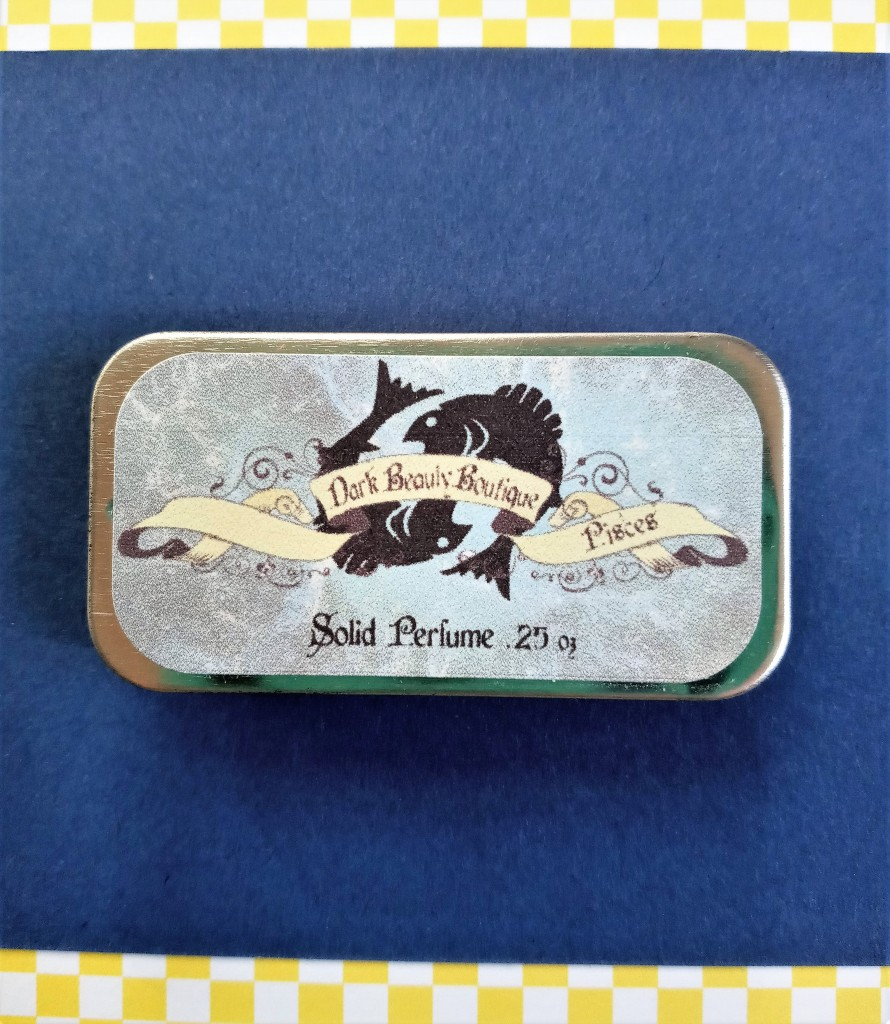 Dark Beauty Boutique Pisces solid perfume, with a label bearing an imageof two fishes.