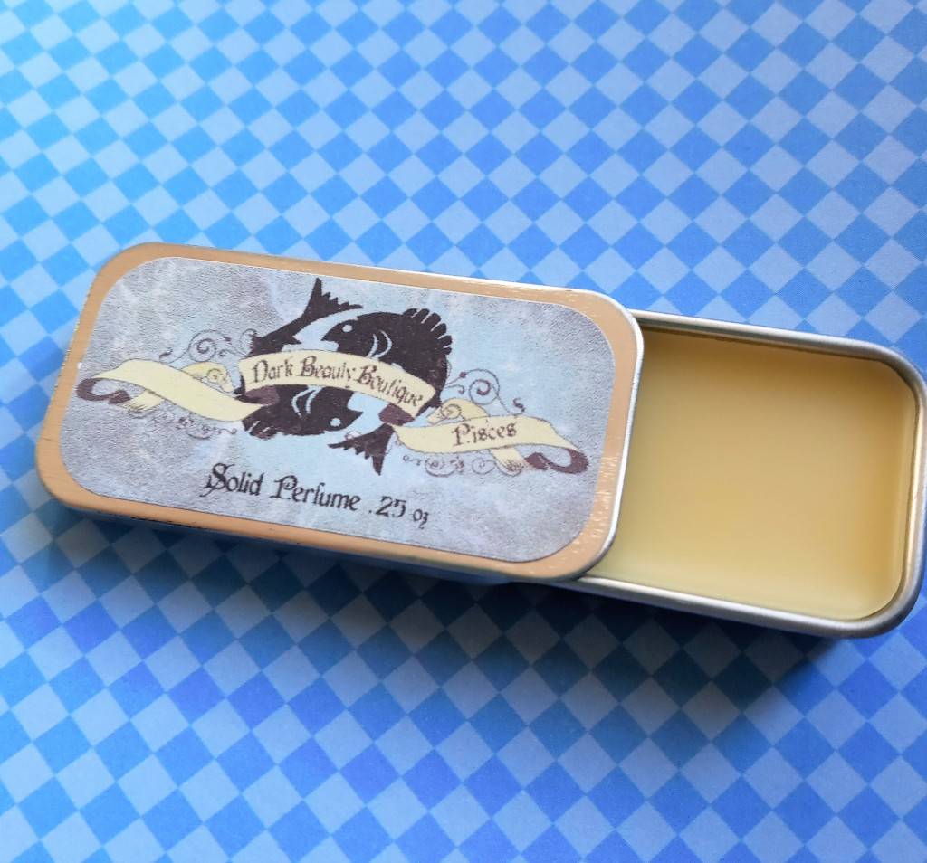 The Pisces perfume tin, opened to reveal the light tan solid perfume inside.