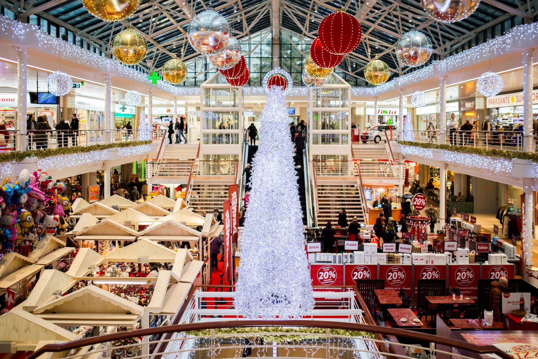 Stock photo of a shopping mall at Christmas time, filled with crowded shoppers, a large Christmas tree and sparkling holiday decorations.
