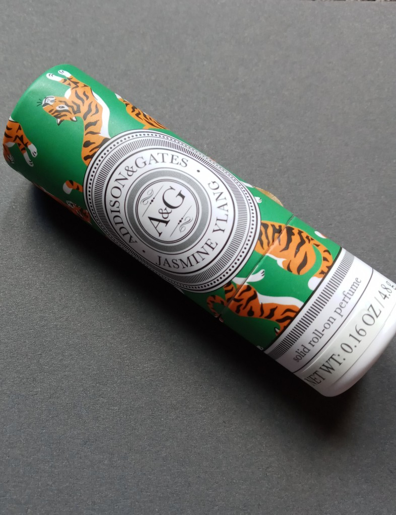 Addison & Gates Jasmine Ylang perfume solid, in a green tube printed with orange and black tiger illustrations
