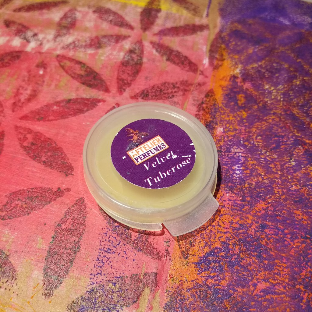 A sample of Aftelier Velvet Tuberose in a plastic compact, against a pink and purple painted background