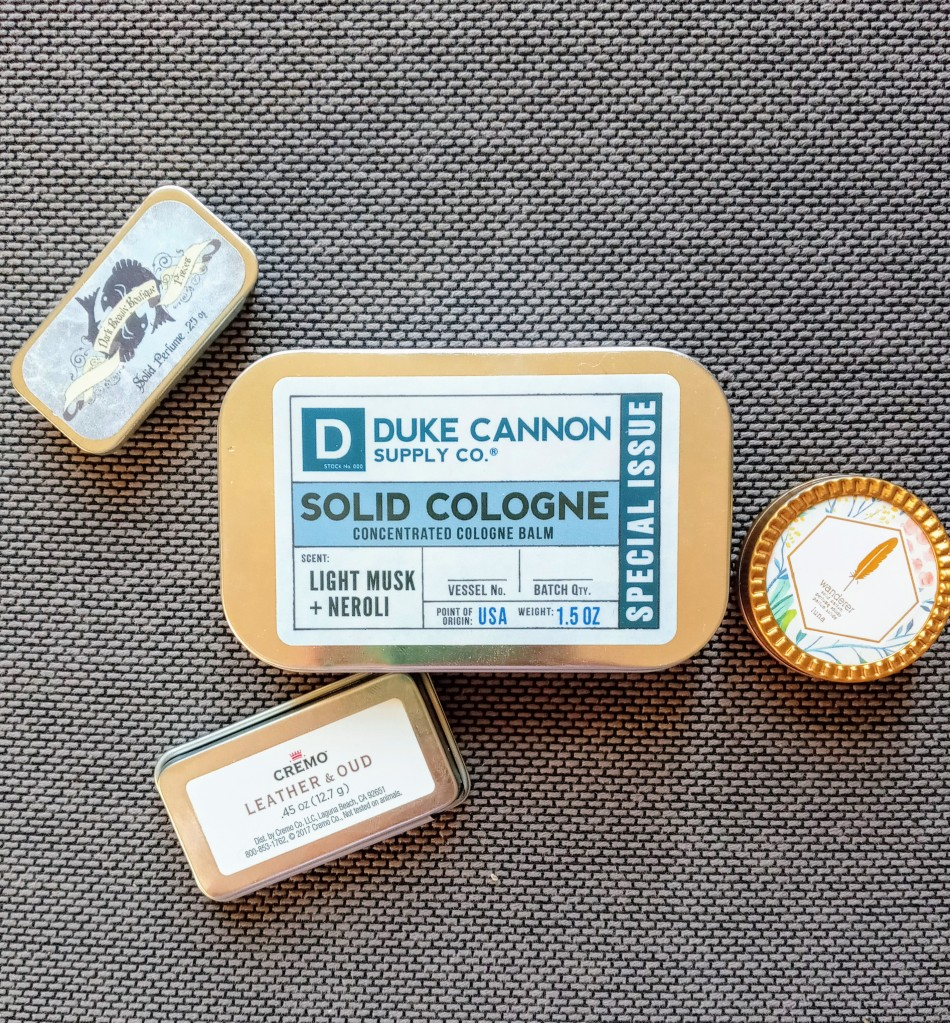 The large 1.5 ounce Duke Cannon tin next to three smaller solid fragrance tins, for a comparison of size
