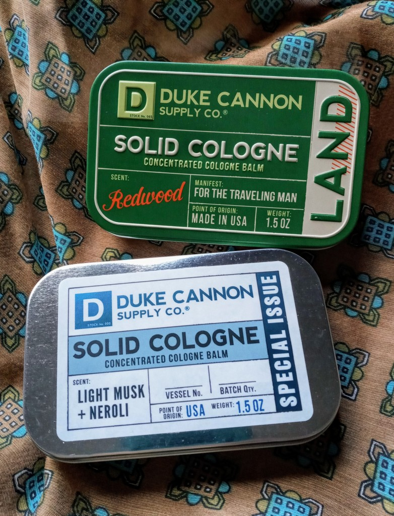 Duke Cannon Land and Light Musk Neroli solid colognes against a brown, green and blue bandana