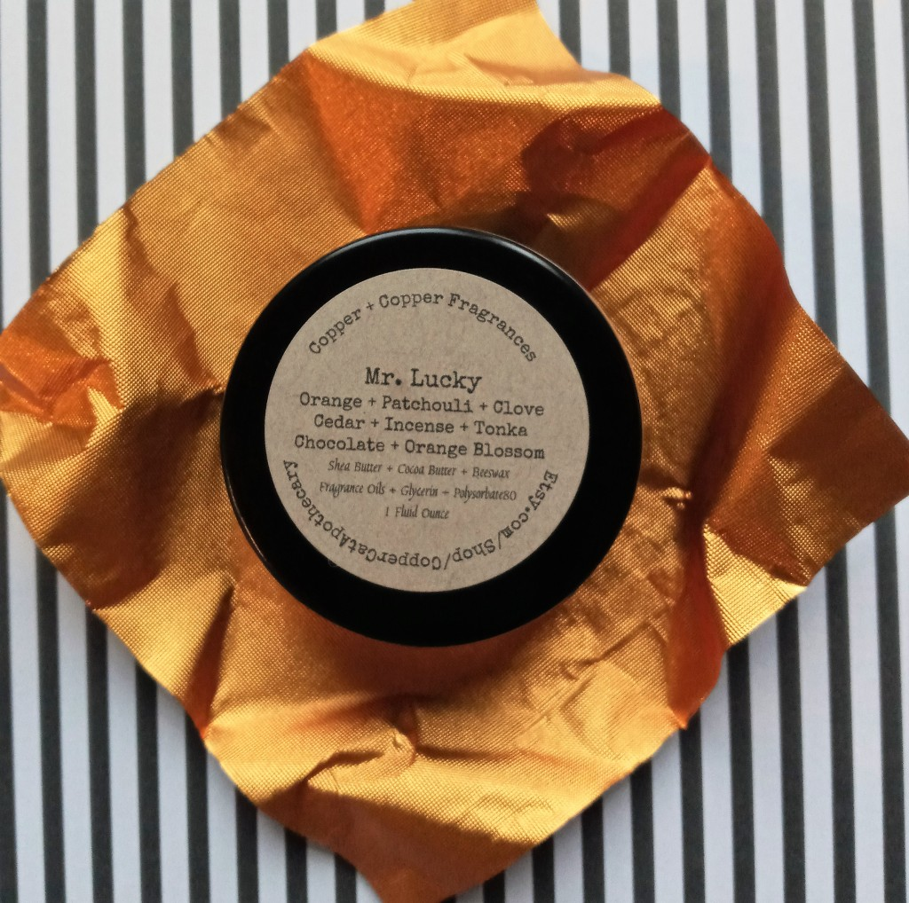 the back of the Mr. Lucky solid perfume, listing the notes and ingredients, against orange paper and black and white paper backgrounds