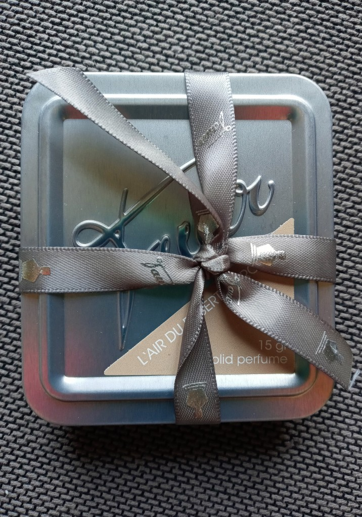 The LDDM solid perfume, tied up in its taupe ribbon
