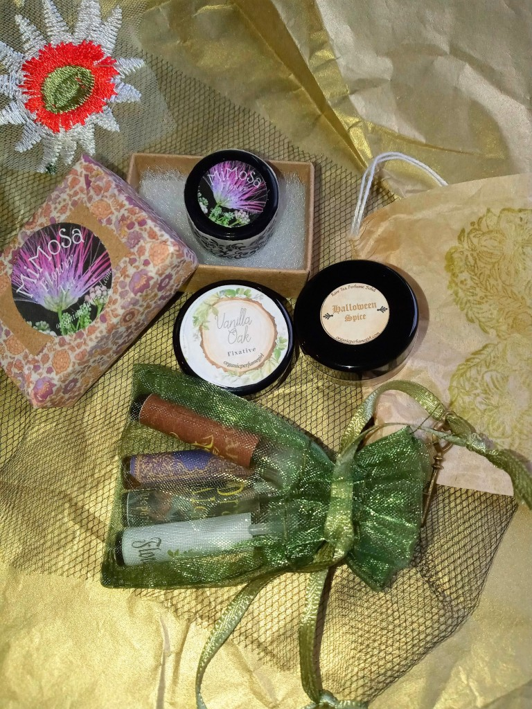 The contents of the box from Organic Perfume Girl, featuring liquid and solid fragrance samples in pretty, Victorian-inspired packaging