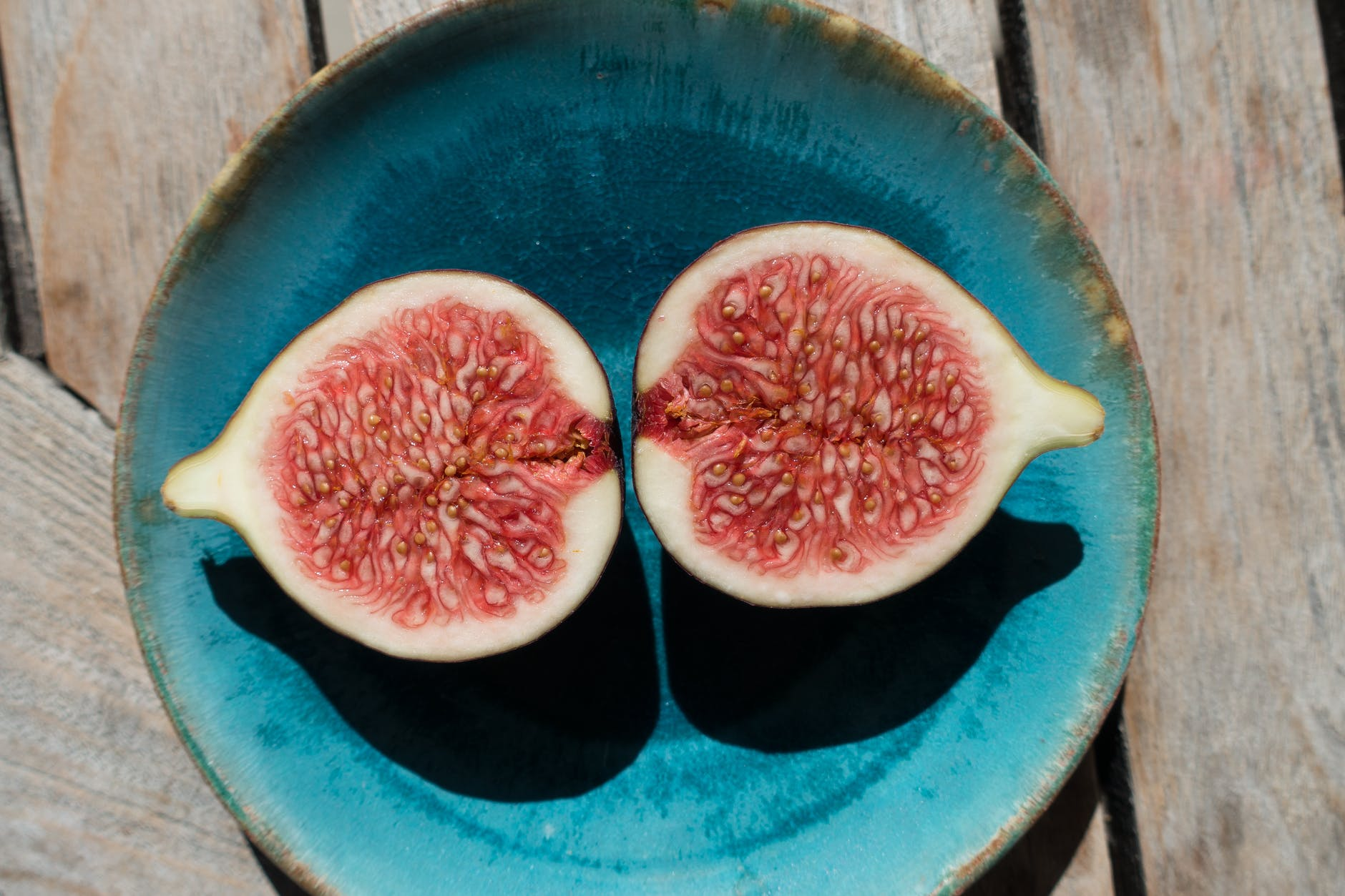 Stock photo of a ripe fig sliced in half, on a blue ceramic plate