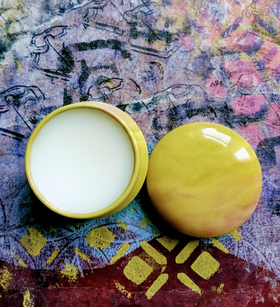 The Wild Fig solid perfume, open against a brightly colored purple background