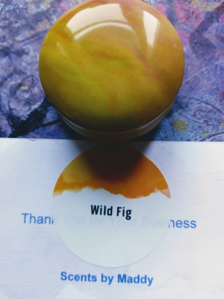 The Wild Fig solid perfume next to the card bearing its name