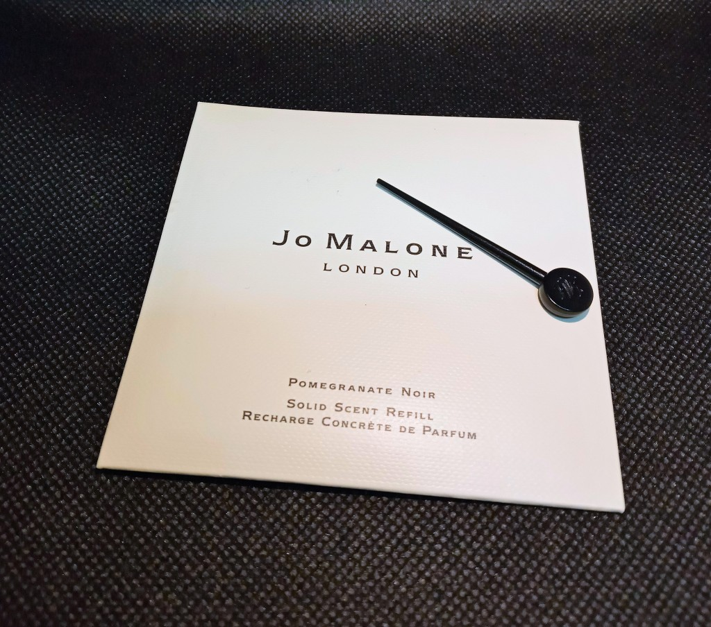 The Jo Malone Pomegranate Noir solid scent refill envelope, along with its plastic pin tool for removing the solid