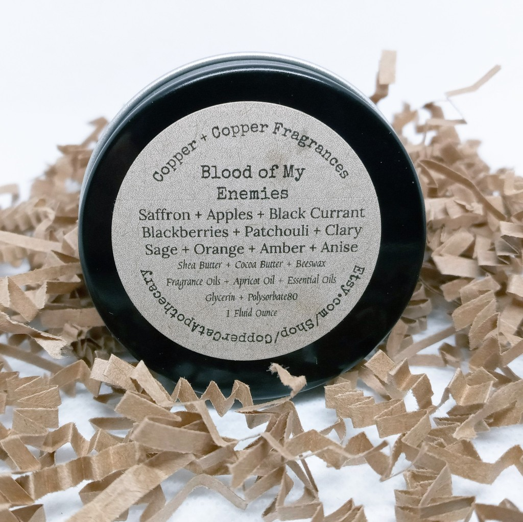 The bottom of the Blood of My Enemies solid fragrance tin, with a tan label listing the fragrance notes and ingredients