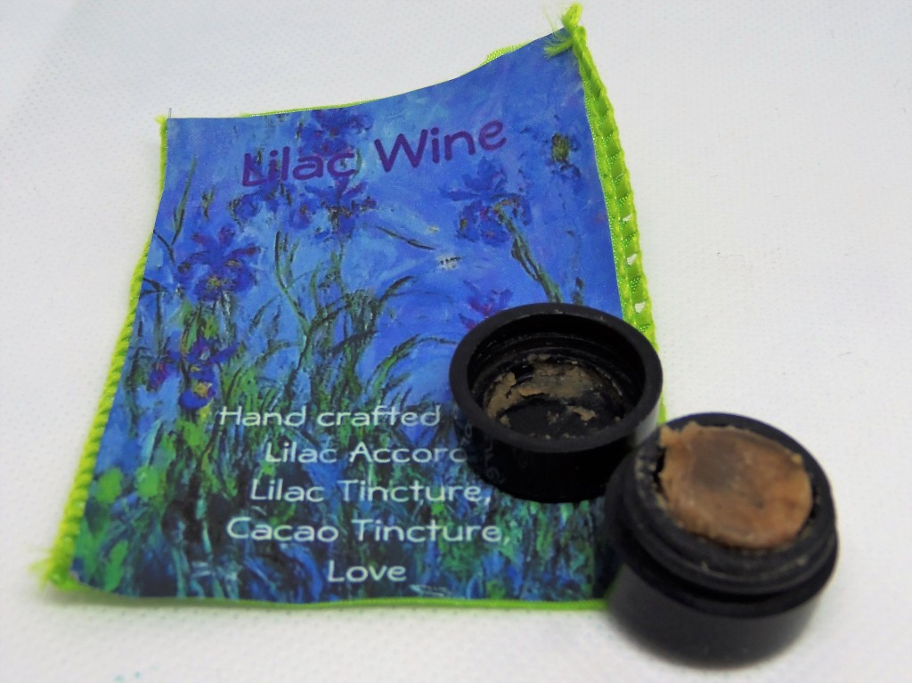 The Lilac Wine perfume, opened to show its dark brown color and paste-like texture, next to a printed card featuring illustrations of lilacs and a list of the notes:  lilac accord, lilac tincture, cacao tincture and love.