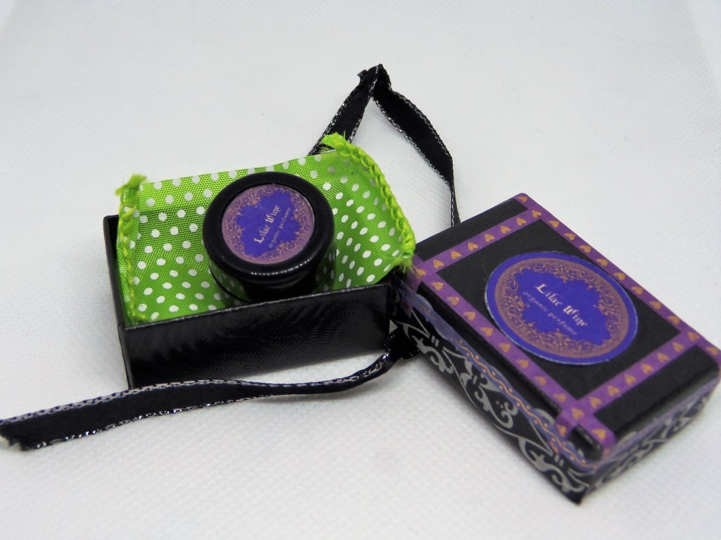 The Lilac Wine box, open, with the perfume inside, atop a green ribbon. The box was tied with a black and silver ribbon.