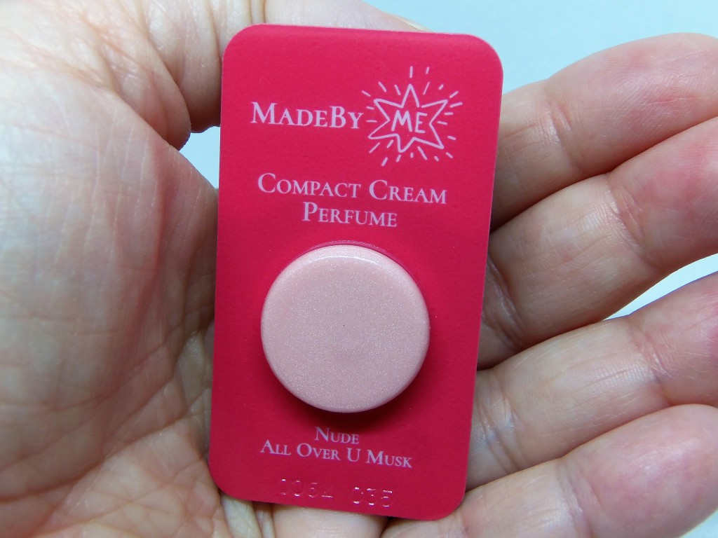 All Over U Musk sample, in a red blister packet with white lettering, held in a woman's hand