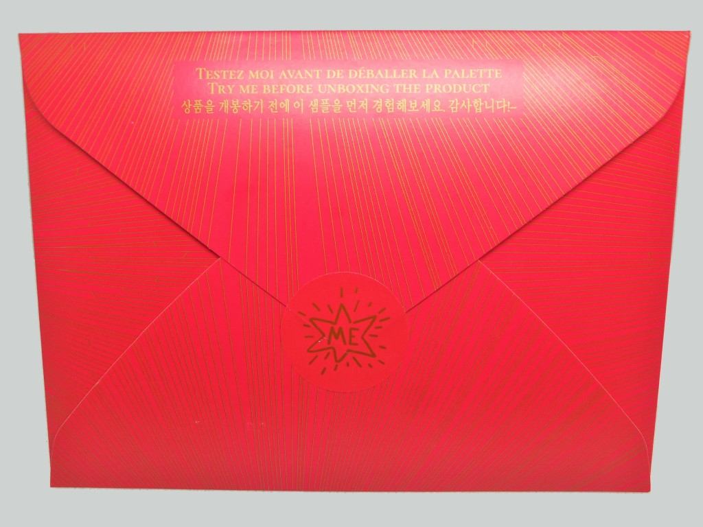 """The back of the Made By Me sample kit, featuring a red envelope sealed with a red sticker, embossed with a whimsical gold star that says, """"ME"""""""
