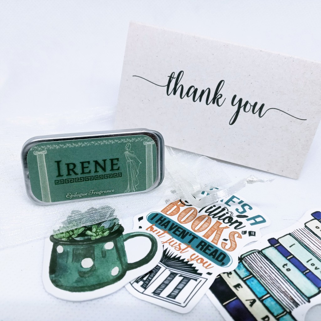 The contents of the perfume bag spread out on a white background, with the perfume, a thank-you card and three literature-themed stickers