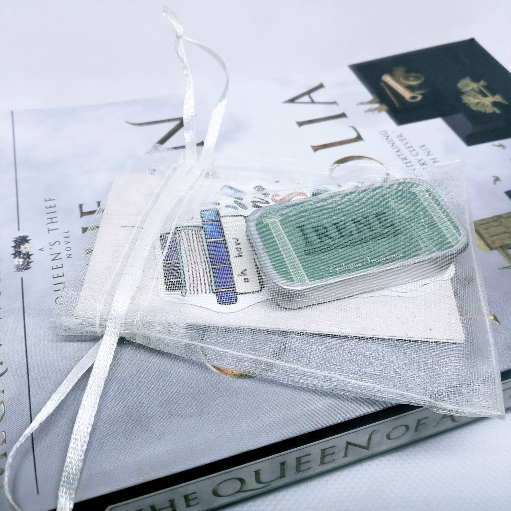 The bag containing perfume and stickers, atop The Queen of Attolia book