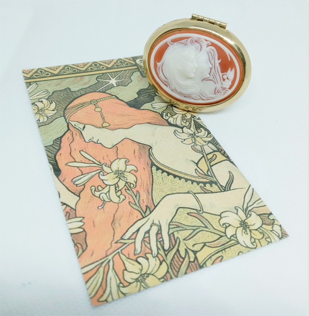 The Magnolia cameo locket, with a cameo featuring silhouettes of two women with flowers in their hair, atop the product card for Magnola