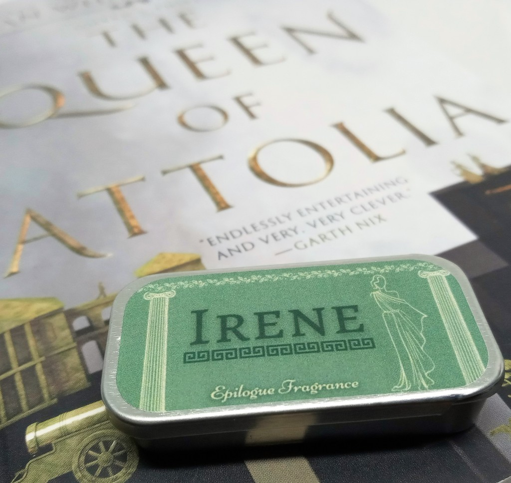A close-up photo of the Irene perfume tin against the front cover of The Queen of Attolia book