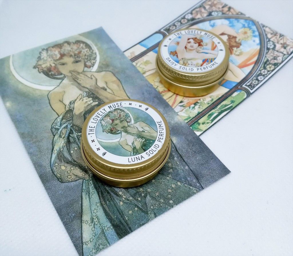 Luna and Daisy try-me tins atop the product cards with larger pictures of the Mucha artwork on the packaging