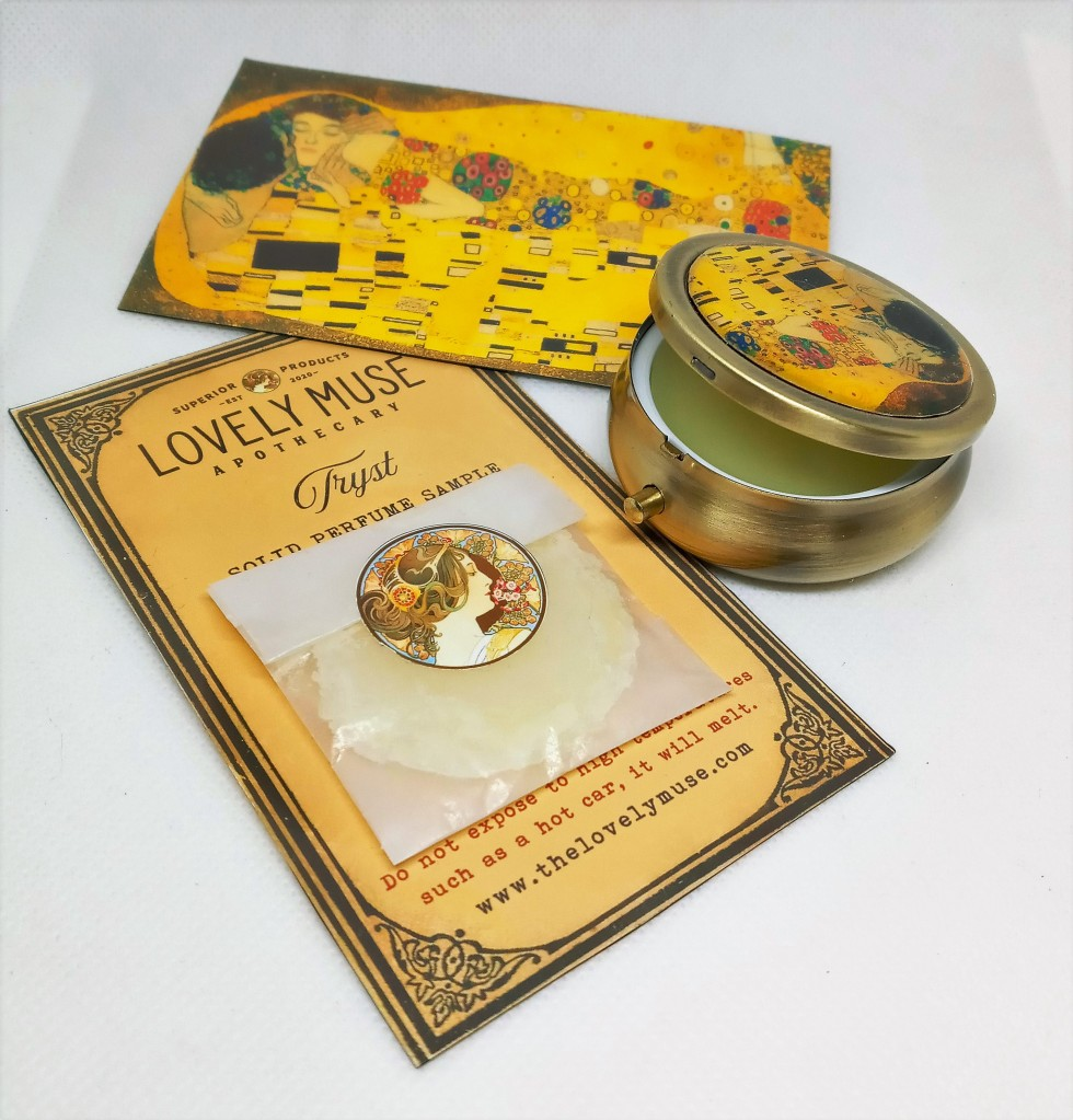 The Tryst locket adorned with Gustav Klimt's The Kiss painting, next to a carded sample of Tryst