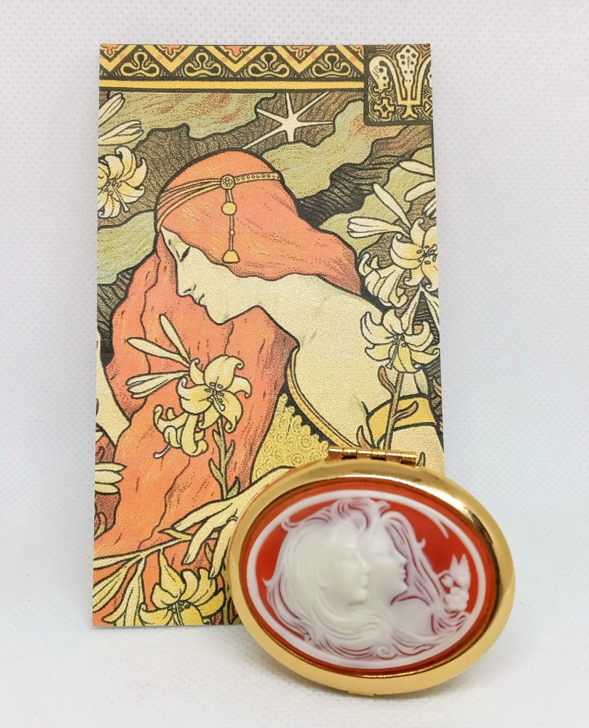 A close-up photo of the Magnolia Cameo in front of the artwork on its product card