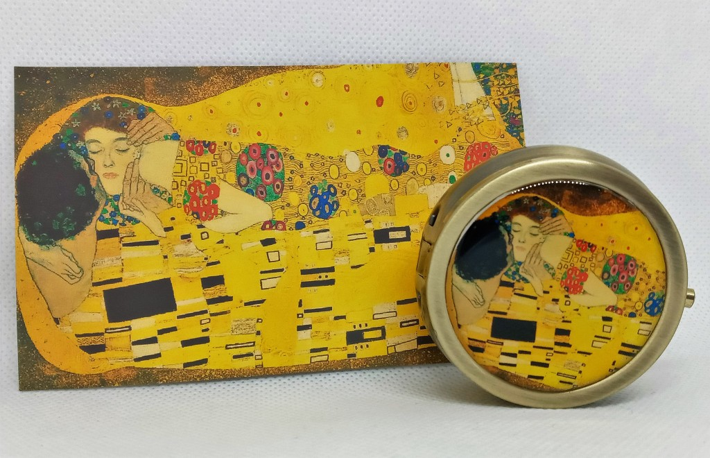 The Tryst locket next to the artwork on its product card