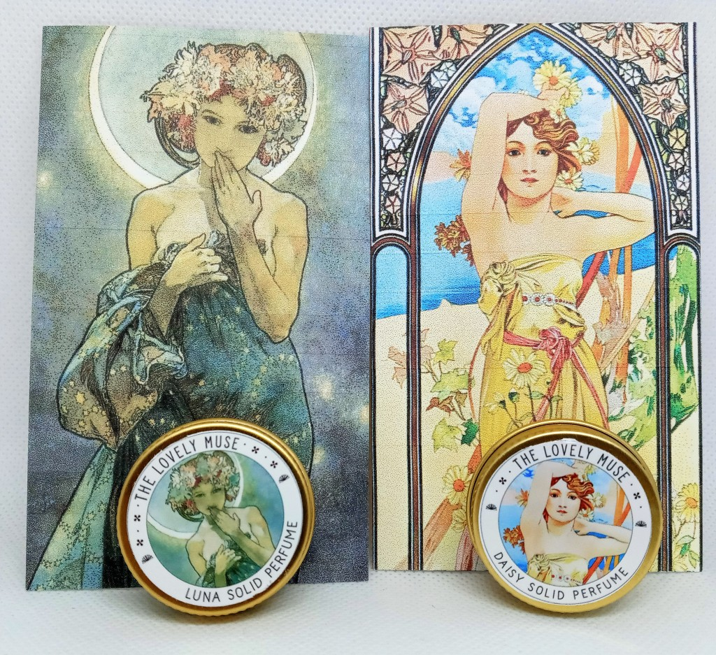 Luna and Daisy tins in front of their artwork